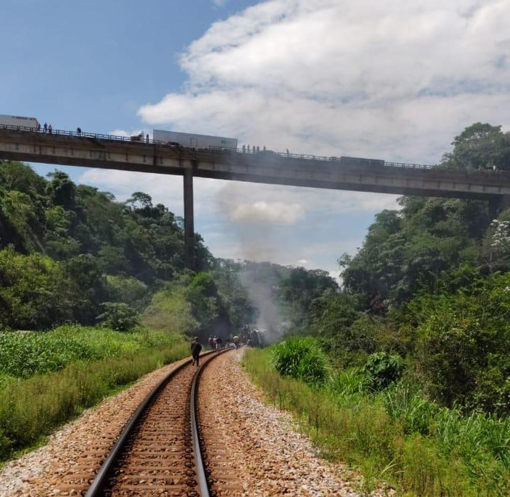 Do alto do viaduto pessoas olham para o ônibus que caiu de um altura de 15 metros perto de uma linha férrea. — Foto: Redes sociais